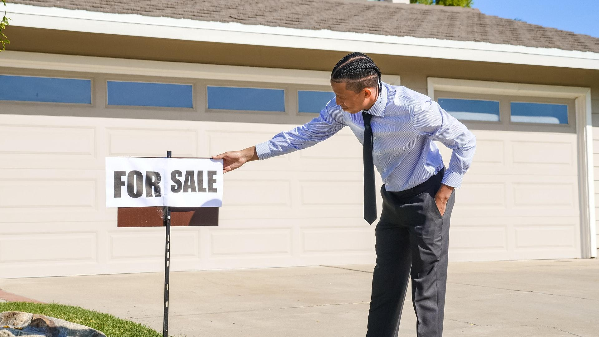 """a real estate agent is hanging a sign """"for sale"""" near of the house"""